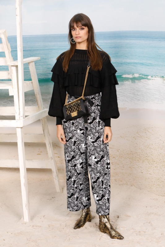 The French singer, CLARA LUCIANI, wore a printed black and white cotton pants with a black layered sweater, both from the from the Fall-Winter 2018/19 Ready-to-Wear collection. CHANEL bag and shoes.