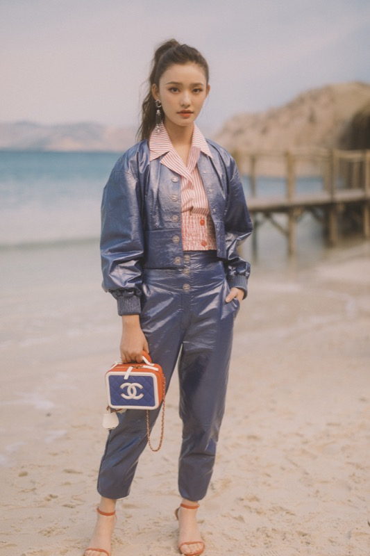 Jelly Lin, CHANEL Ambassador, wore metallic blue pants & top & pink blouse, look 49, from the Cruise 2019 Ready-to-Wear collection. CHANEL bag & accessories.