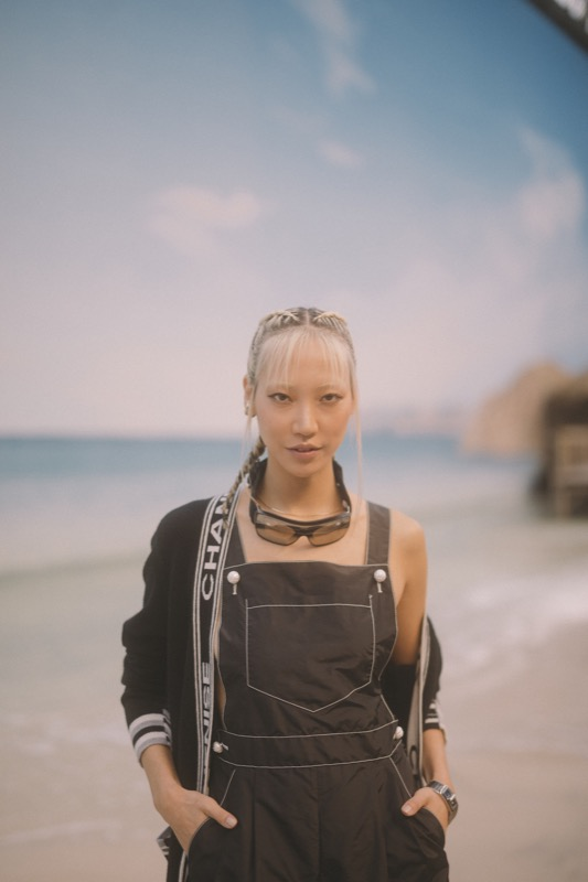 Soo Joo Park, CHANEL Ambassador, wore a black jumpsuit & top, look 99, from the Spring-Summer Act 1 2019 Ready-to-Wear collection. CHANEL bag & accessories. CHANEL Watches, Code Coco in steel, black ceramic and one princess cut diamond.