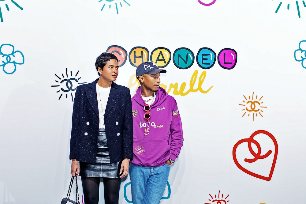 Pharrell Williams wore a purple embroidered sweater and accessories from the CHANEL-Pharrell capsule collection.